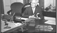 A Recreation of President Harry S. Truman's desk, with the late president posing there