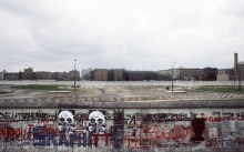 A picture taken 29 April 1984 shows various graffiti painted on the Berlin Wall on the West Berlin side while East German and Soviet flags (R) fly on the other side of the East Berlin no-mans-land spiked with anti-tanks traps AFP Photo Joel Robine