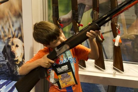 A boy under his parents' supervision, aims a shotgun April 11, 2015 at the 2015 NRA Annual Convention in Nashville, Tennessee. (Photo credit KAREN BLEIER/AFP/Getty Images)