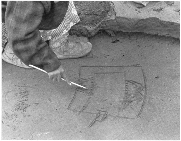 A girl uses a story knife for drawing pictures in the ground to illustrate a story. Bethel, 1936. Hans Himmelheber, Courtesy of Eberhard Fischer and Anchorage Museum, HH28.