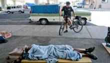 A Boise police officer stops his bike in front of homeless residents under the South 16th Street bridge in September 2014. (Photo credit: Idaho Statesman)