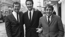 Bob Shane, left, with other members of the Kingston Trio — John Stewart, center, and Nick Reynolds — in Hollywood in 1967. The group spearheaded a folk revival in the late 1950s. Mr. Shane, Mr. Reynolds and Dave Guard were the original members; Mr. Stewart replaced Mr. Guard in 1961.Credit...Associated Press